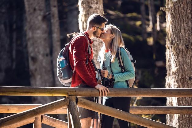 Due escursionisti di viaggio con zaino che si baciano stando in piedi sul ponte di legno nella foresta.