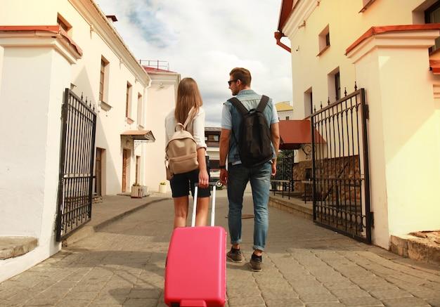 Due viaggiatori in vacanza in giro per la città con i bagagli.
