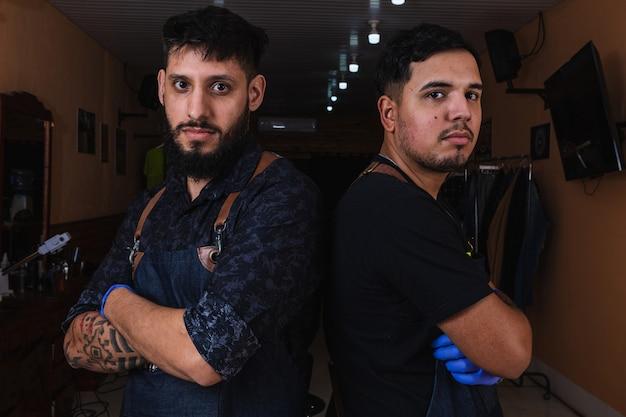 Due parrucchieri professionisti di fiducia in piedi nel salone con le braccia incrociate