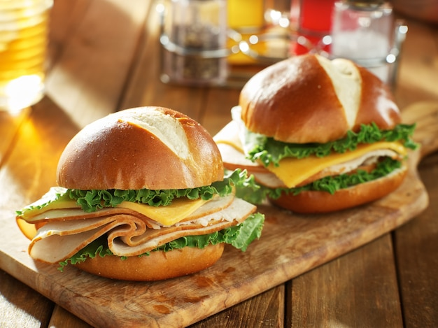 Due panini di tacchino e formaggio su focacce pretzel