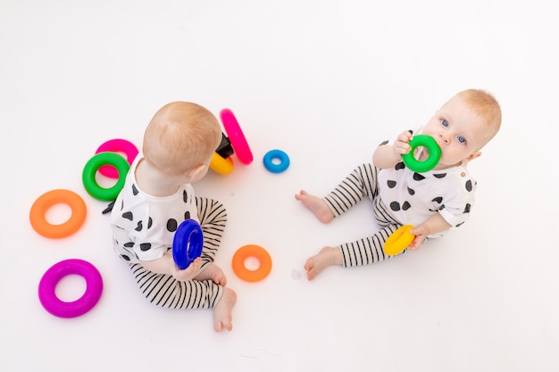 Due bambini gemelli di 8 mesi giocano su uno sfondo bianco isolato, sviluppo precoce di bambini fino a un anno, un bambino prende un giocattolo da un altro, un posto per il testo