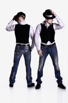 Due fratelli gemelli in posa stile gangster. cappelli, gilet, camicie bianche. sfondo bianco.