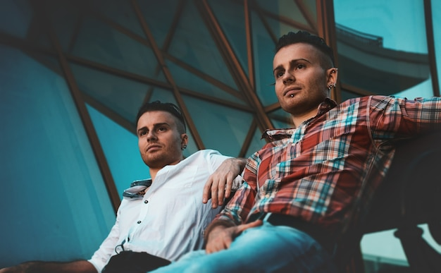 Due fratelli gemelli si siedono sullo sfondo di un grattacielo blu e guardano in lontananza. camicie e pantaloni. giovani imprenditori