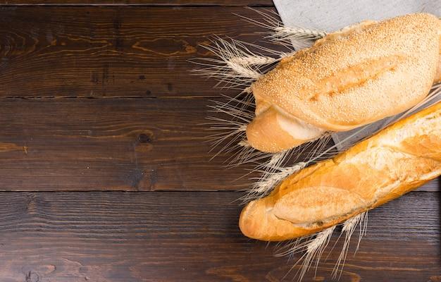 Due tipi di pagnotte baguette con fessure sulla parte superiore e semi di sesamo tra i gambi di grano intero su tavola marrone scuro