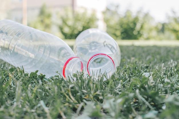 Due bottiglie di plastica usate sullo sfondo dell'erba
