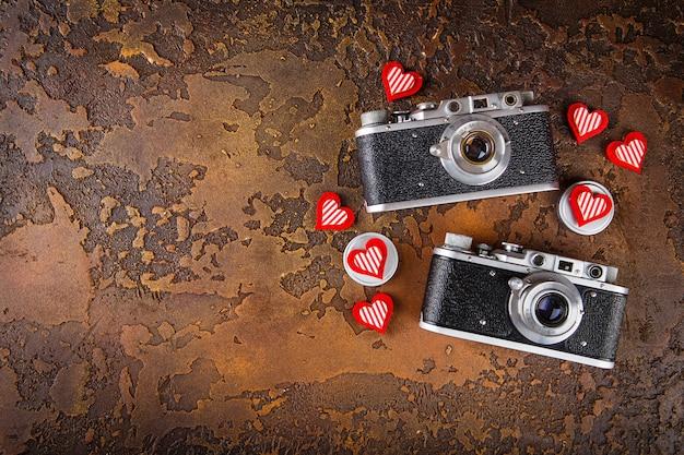 Due macchine fotografiche retrò vintage e cuori sul tavolo di cemento marrone. san valentino. vista dall'alto