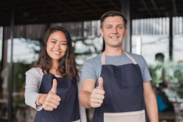 Due camerieri che mostrano il pollice in su insieme stando in piedi davanti al loro caffè