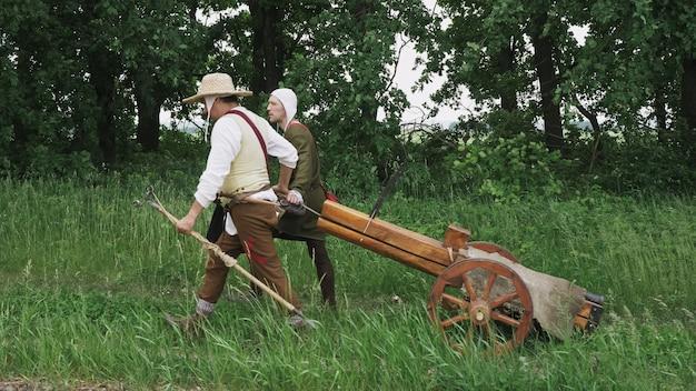Due guerrieri stanno trascinando un cannone lungo un sentiero nel bosco. ricostruzione storica