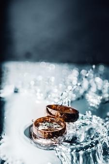 Due anelli di nozze d'oro in acqua spruzza posa su una superficie piana