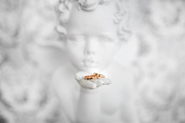 Due anelli di nozze in mano d'angelo, foto da vicino