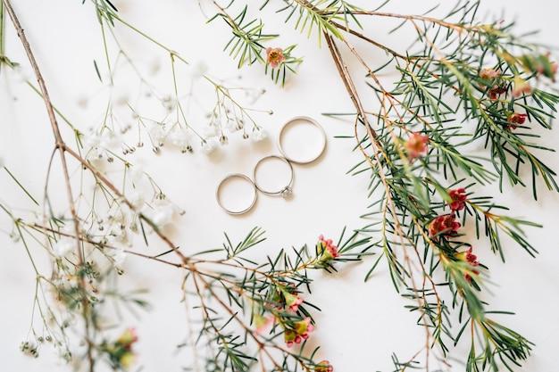 Due fedi nuziali per la sposa e lo sposo e l'anello di fidanzamento della sposa su uno sfondo bianco con
