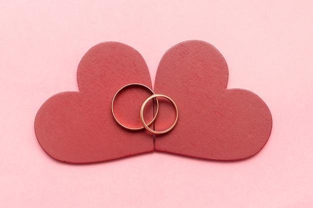 Due anelli di nozze su cuori rossi su sfondo rosa san valentino, fidanzamento, matrimonio, matrimonio. concetto di amore.