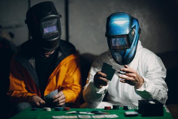 Due saldatori in maschere di saldatura giocano a poker.