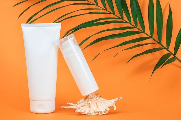 Due bottiglie cosmetiche in bianco bianche, conchiglie e foglie di palma verdi sulla superficie arancione