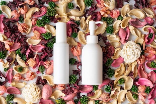 Due bottiglie bianche poste su fiori secchi sparsi dappertutto