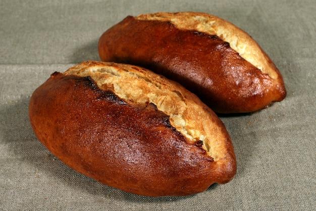 Due pane bianco si trovano su una tovaglia di lino grigia