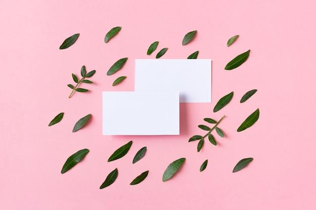 Due biglietti da visita bianchi su sfondo rosa con foglie verdi.