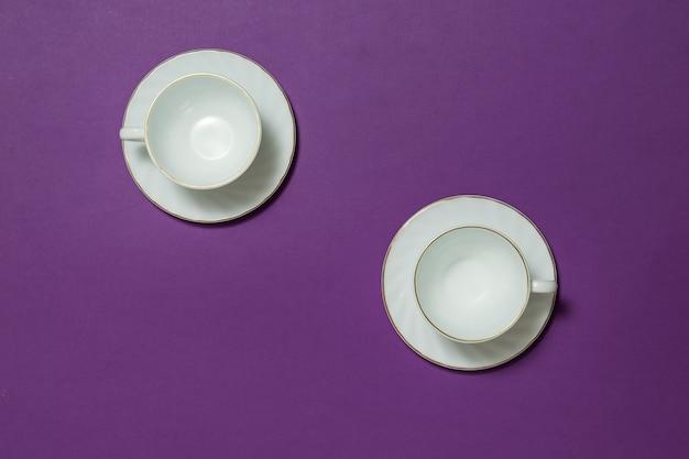 Due tazze da caffè in ceramica bianca su sfondo viola. piatti per bevande calde.