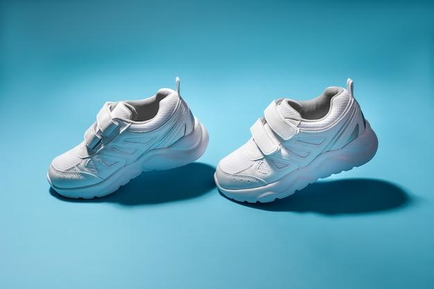 Due bambini bianchi che volano in aria scarpe da ginnastica simulano di camminare isolati su uno sfondo blu
