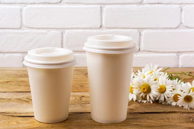 Due bicchieri di carta calda usa e getta per caffè bianco con coperchio mockup con fiori di campo margherita