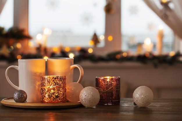 Due tazze bianche con decorazioni natalizie sullo sfondo della finestra