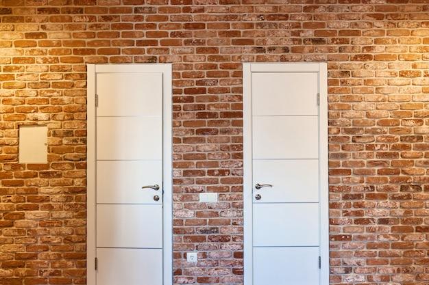 Due porte bianche in un muro di mattoni. due porte.
