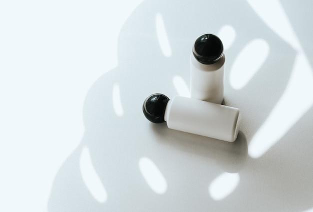 Due bottiglie di plastica vuote bianche su un bianco con un'ombra di una foglia tropicale
