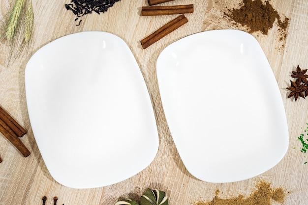 Due piatti vuoti bianchi su un tavolo di legno chiaro con cibi decorativi intorno