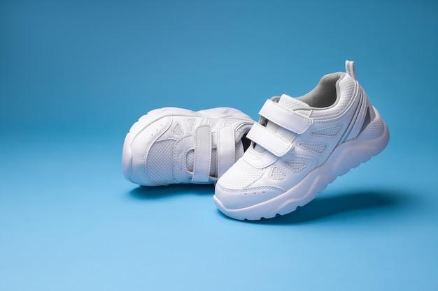 Due sneakers bianche da ragazza una sneaker che vola in aria e l'altra sdraiata su un fianco isolata su...