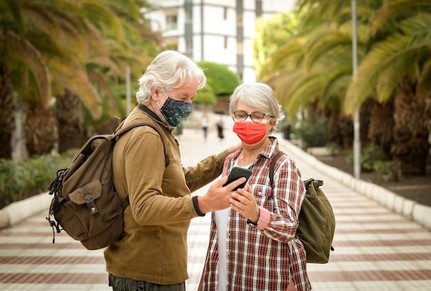 Due viaggiatori senior dai capelli bianchi con lo zaino sulle spalle che guardano insieme allo smartphone. pensionati attivi che si godono la passeggiata in città