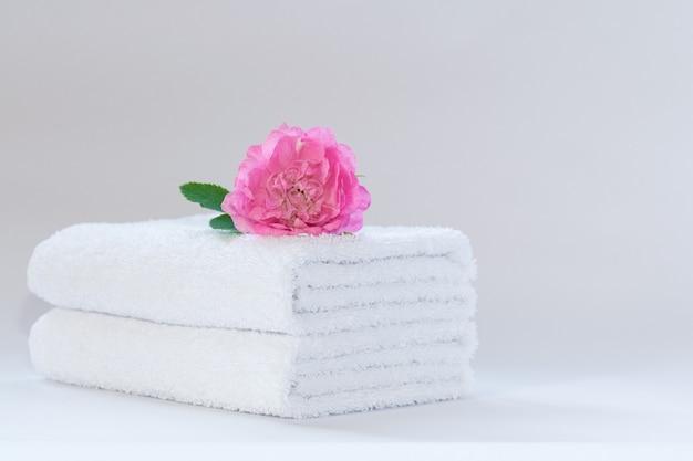 Due asciugamani di spugna bianchi ben piegati con un fiore di rosa