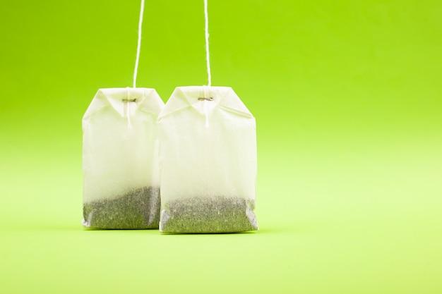 Due sacchi di carta bianco con tè nero su uno sfondo verde chiaro copia spazio, primo piano.