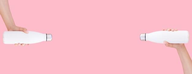 Due bottiglie di acqua termica in acciaio bianco in mano sulla superficie rosa pastello. foto panoramica con copia spazio.