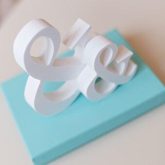 Due simboli bianchi e con una confezione regalo di colore turchese sul tavolo