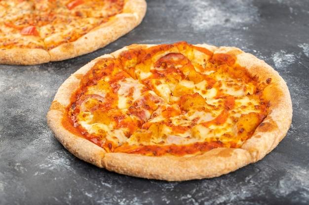 Due intere pizze di pollo disposte su sfondo di pietra.