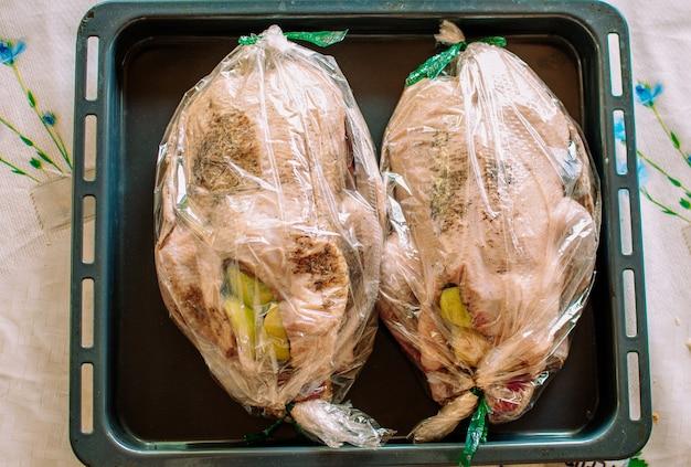 Due anatre intere fresche e crude su un vassoio con ingredienti e spezie per la cottura. anatra alla pechinese con ripieno di mele prima di andare al forno. il concetto di ricette di cucina.