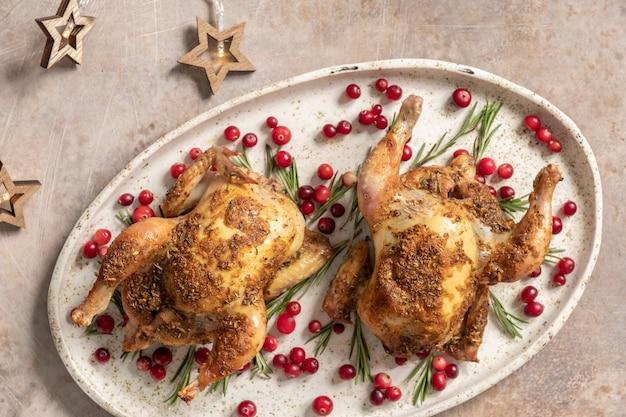Due interi pollo arrosto con mirtilli rossi e fette d'arancia.