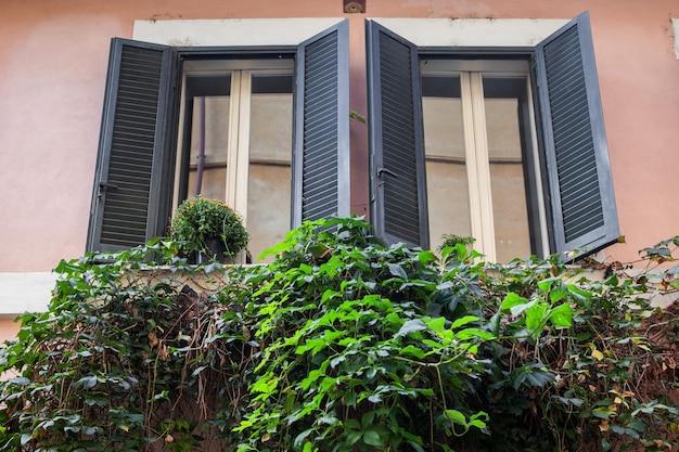 Due finestre rappresentate in antico palazzo o casa a roma
