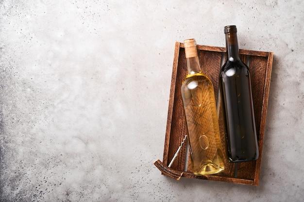 Due bottiglie di vino con uva e bicchieri di vino sul vecchio sfondo grigio tavolo in cemento con spazio copia. vino rosso con un tralcio di vite. composizione del vino su fondo rustico. modello.