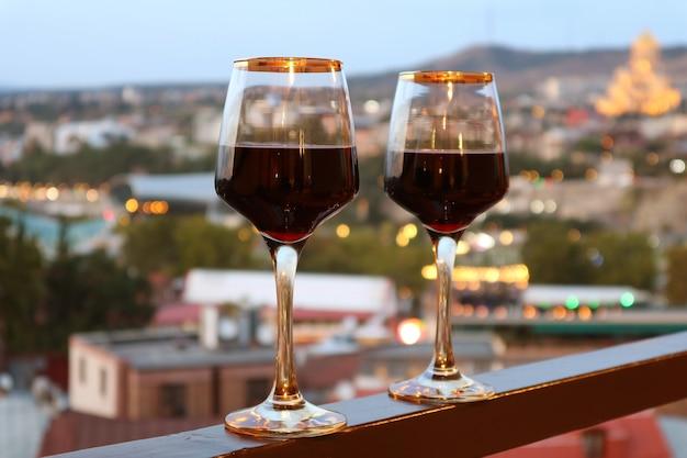 Due bicchieri di vino sul balcone con vista sulla città di sera sfocata