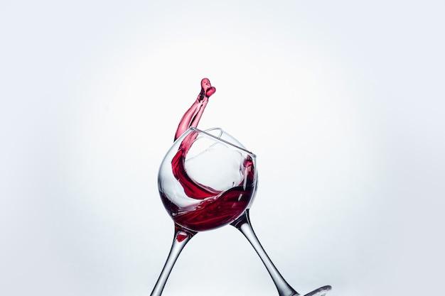 Due bicchieri di vino nel gesto di tostatura con grandi spruzzi in studio.