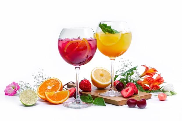 Due bicchieri di vino con frutta estiva e cocktail di frutti di bosco su sfondo bianco