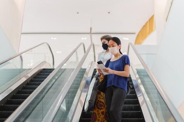 Due donna in maschera protettiva con borse della spesa in piedi sulla scala mobile.