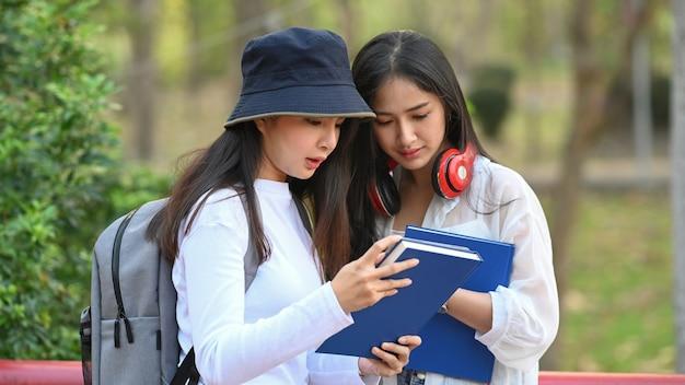 Due donne che leggono un libro nel parco