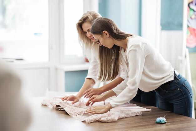 Due donne si sporgono sul tavolo da cucito laboratorio di sarti di moda