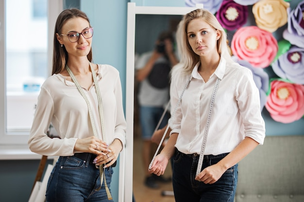 Due donne sono in piedi davanti allo specchio con tapelines sul collo laboratorio di sartoria di moda