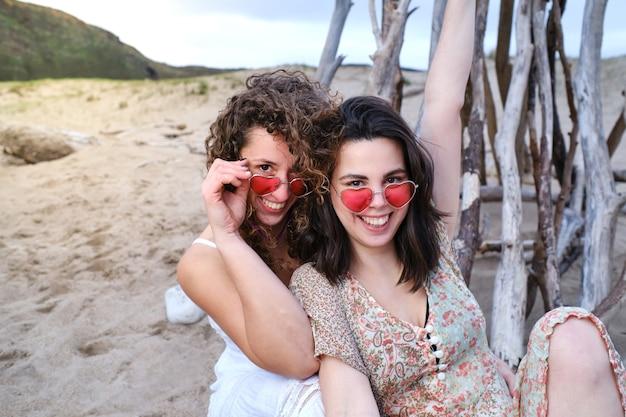 Due donne sulla spiaggia con occhiali a forma di cuore