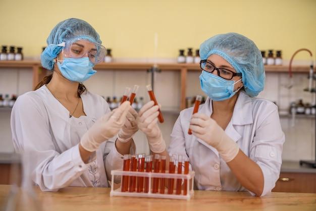 Due donne nel laboratorio di chimica che esaminano le provette con sostanza rossa