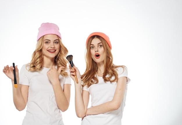Due donne cosmetici sfondo chiaro stile di vita moda glamour