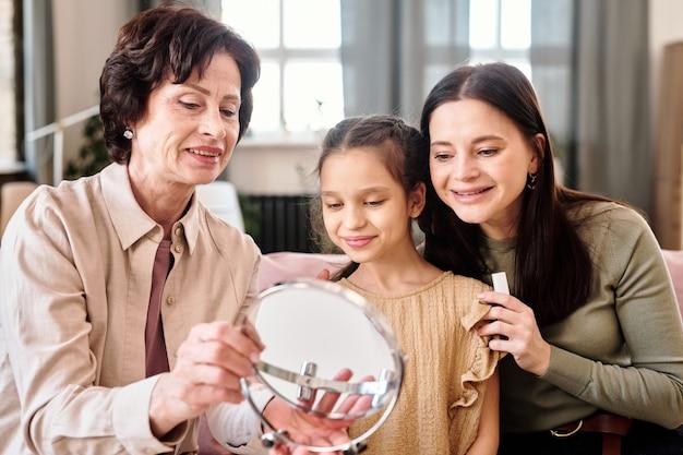 Due donne e una bambina carina che si guardano allo specchio mentre applicano il trucco